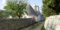 Cycling past a traditional styled trulli house in Puglia