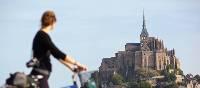 Young woman on a bike admiring Mont Saint Michel | Pierre Torset