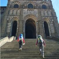 Hikers on the steps of the cathedral in Le Puy en Velay, the traditional start of the Way of St James | Kate Baker
