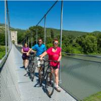 Cyclists crossing the Passerelle Himalayenne, the suspension bridge at Rochemaure enroute to Orange