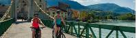 Cyclists crossing the bridge at the pretty town of Seyssel on the Rhone River