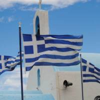 Greek flags flying above a white washed church in the Peloponnese