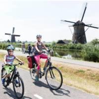 Family cycling past the windmills at Kinderdijk   Inge van Mill