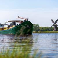 La Belle Fleur making its way along a canal in Holland with a windmill in the background