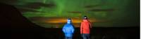 Travellers watching the breathtaking Northern Lights in a remote part of Iceland