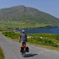 Cyclists on the west Cork coastline with rolling hills and stunning coastline