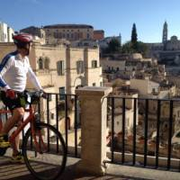 Cyclist viewing the historic cave dwellings in the Sassi di Matera   Kate Baker