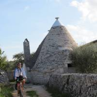 Cyclist passing a trulli house in Puglia   Kate Baker
