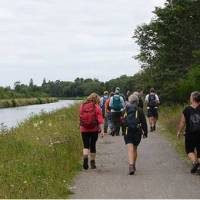 Walkers on the towpath to Inverness with the comfortable barge Fingal