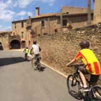 Family cycling through a village in Catalonia on a self guided cycle trip | Kate Baker