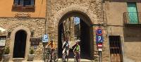 Family group cycling in a village in Catalonia on a self guided holiday | Kate Baker