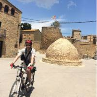 Man cycling through the village of Palau Sator in Catalonia on a self guided cycle holiday | Kate Baker