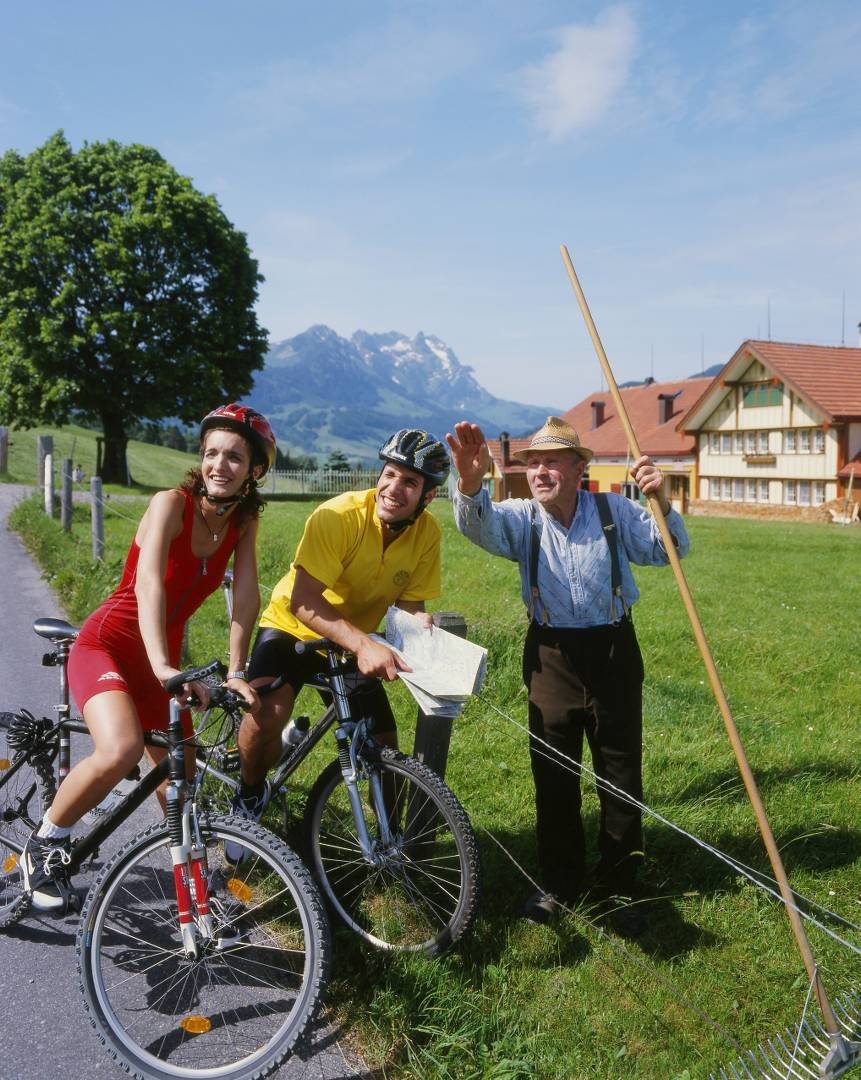 Cyclists getting directions from a local farmer in Switzerland
