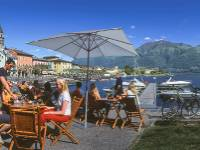 Cyclists taking a break at a cafe by Lake Maggiore in the Ticino region