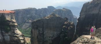 Hikers above a precipitous ridge overlooking Varlaam Monastery in Meteora | Kate Baker