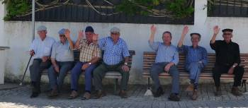 Cycling by old men resting on park benches in the Alentejo