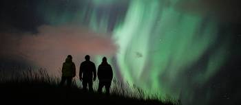 Travellers admiring the phenomenon of the Aurora Borealis in Iceland